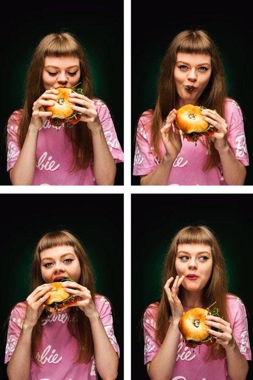 Budapest Bagel - girl eating a bagel